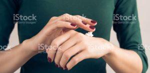 maroon manicure applying hand cream